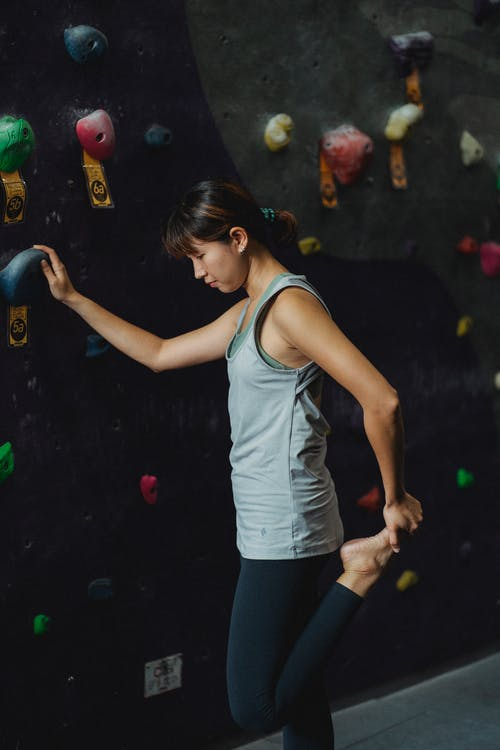 Side view of concentrated young fit ethnic female climber in sportswear stretching legs while standing near artificial wall before ascending in modern gym
