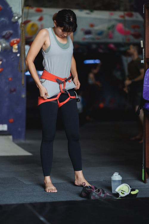 Barefooted ethnic sportswoman in safety equipment before climbing in gym