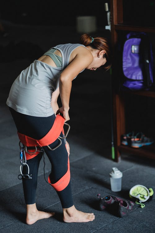 Side view of young sporty barefooted ethnic female in activewear wearing sit harness while preparing for climbing in modern gym