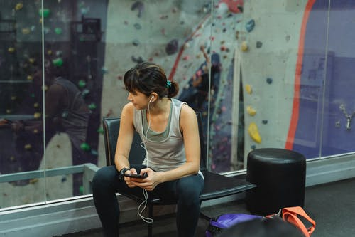 Smiling young ethnic lady in earphones talking on smartphone during break in gym