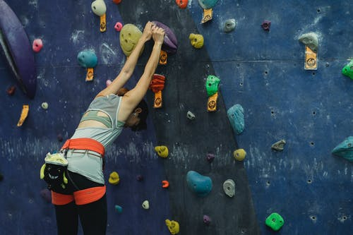 Back view of unrecognizable young slim female climber in activewear and safety sit harness hanging on wall during bouldering in gym