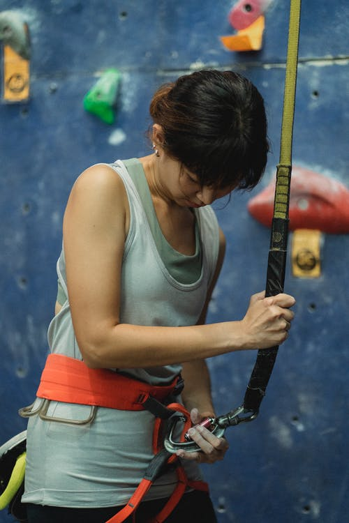 Focused young Asian sportswoman in activewear fastening belay rope to sit harness while preparing for climbing wall in gym