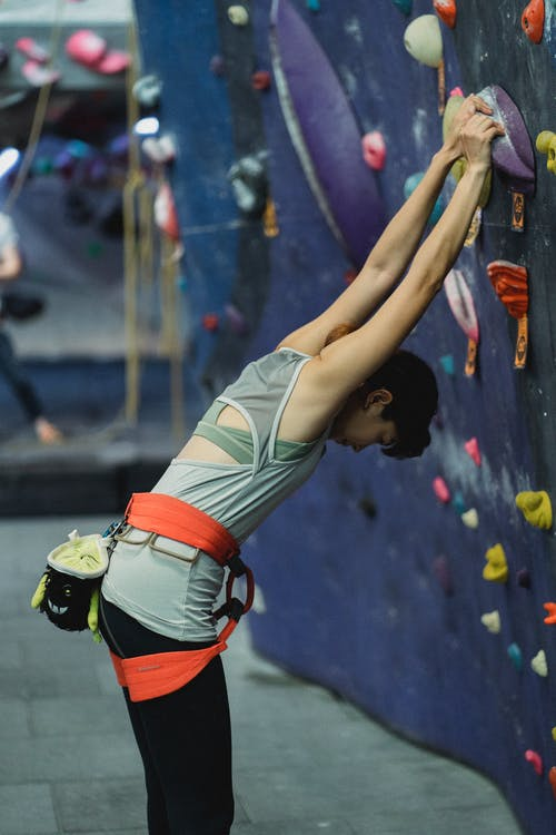 Side view of young sporty lady in activewear and safety harness stretching body before climbing wall in bouldering center