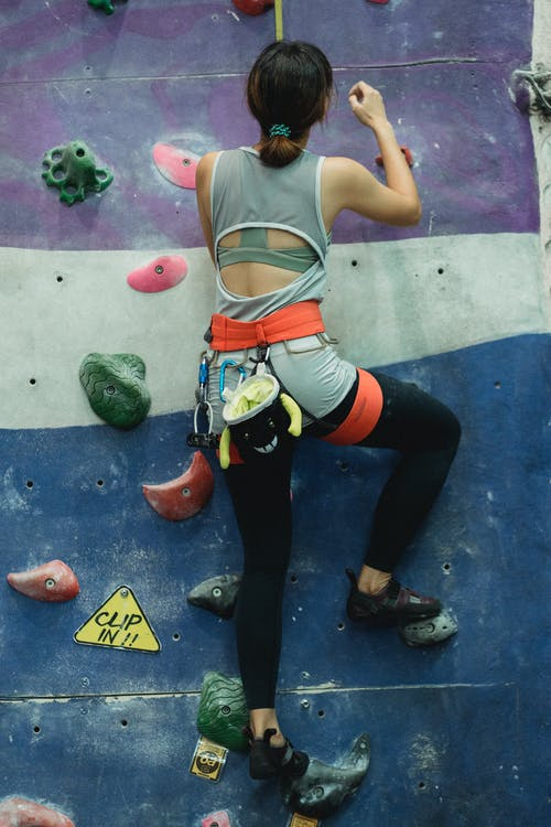 Unrecognizable female boulderer climbing wall in gym