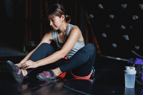 Young Asian sportswoman wearing sneakers sitting on mat in climbing club