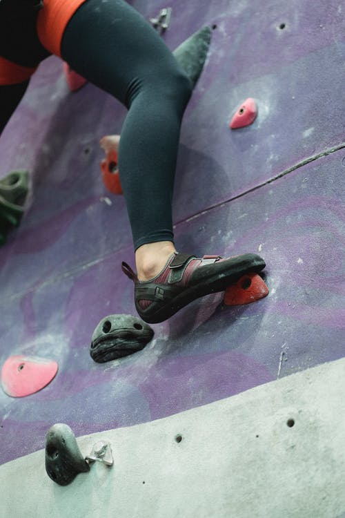 From below of crop unrecognizable female alpinist in sportswear and safety harness practicing climbing on artificial rock wall in gym