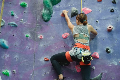 Unrecognizable female climber ascending wall in bouldering gym