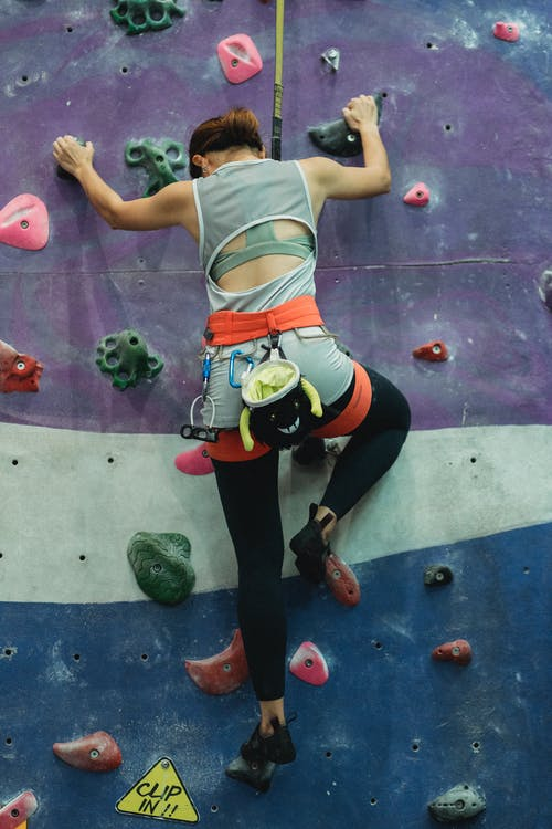 Anonymous sporty lady practicing bouldering in climbing gym