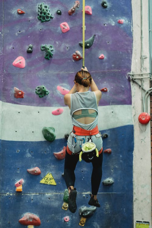 Back view of unrecognizable female climber in activewear and sit harness hanging on rope during bouldering workout in gym
