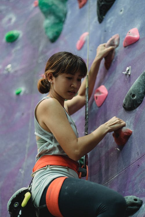Focused young ethnic female climber ascending wall in modern gym