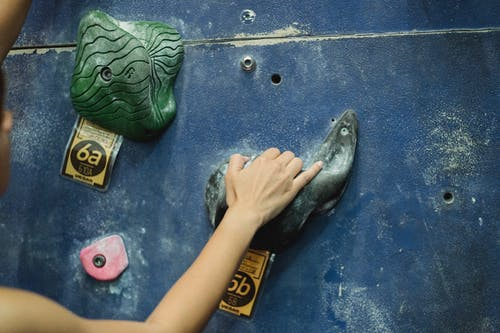 Unrecognizable woman practicing indoor climbing in gym