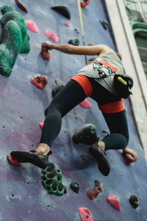 Faceless fit sportswoman climbing colorful wall in gym