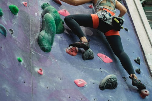 Low angle of crop unrecognizable sportswoman in activewear and safety harness ascending wall while training in climbing gym