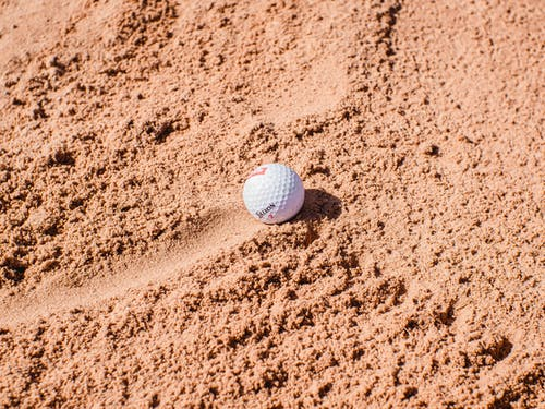 White Golf Ball on Brown Sand