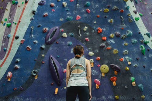 Back view of anonymous young female athlete in sportswear standing against colorful climbing wall and looking up before training in gym