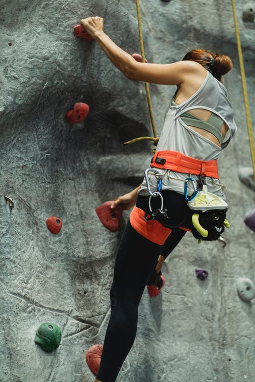 Anonymous fit female alpinist practicing bouldering in climbing gym