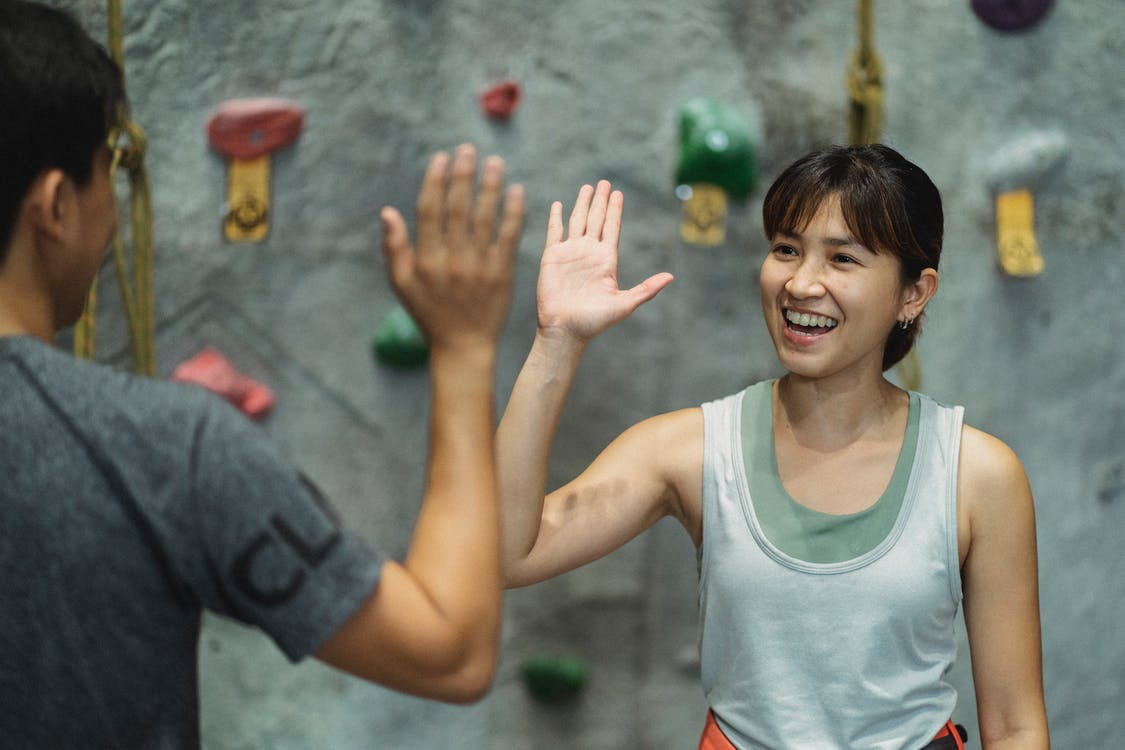 Cheerful young Asian female athlete smiling and giving high five to unrecognizable instructor after climbing workout in gym