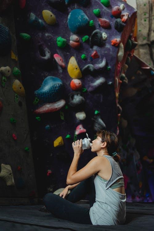 Resting Asian woman near climbing wall