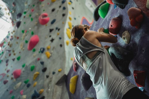 Anonymous woman hanging on climbing wall