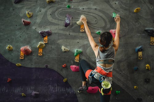 Unrecognizable lady climbing artificial wall in modern gym