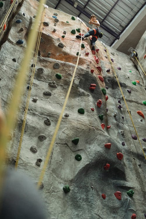 Anonymous determined climber gesturing on high artificial wall in gym