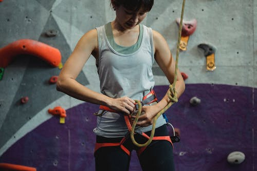 Crop young Asian sportswoman in activewear and safety sit harness preparing belay for climbing training in gym
