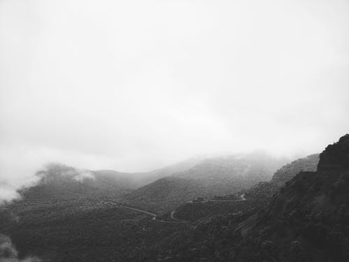 Grayscale Photo of Mountains Under Cloudy Sky