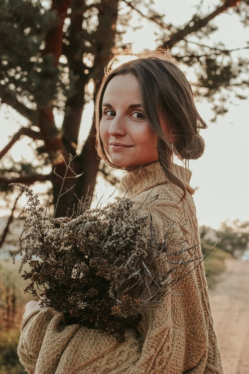 Woman in Brown Sweater Holding Brown and White Plant