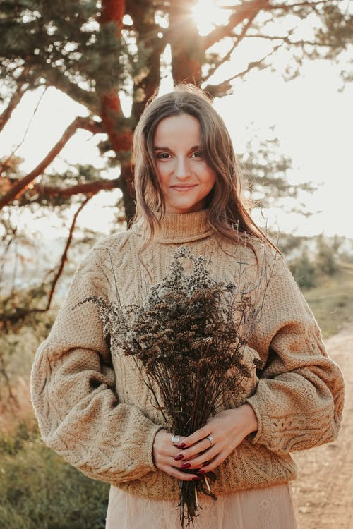 Woman in Brown Sweater Holding Brown Plant