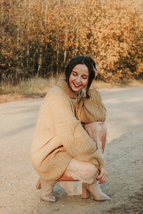 Woman in Brown Sweater Sitting on Road