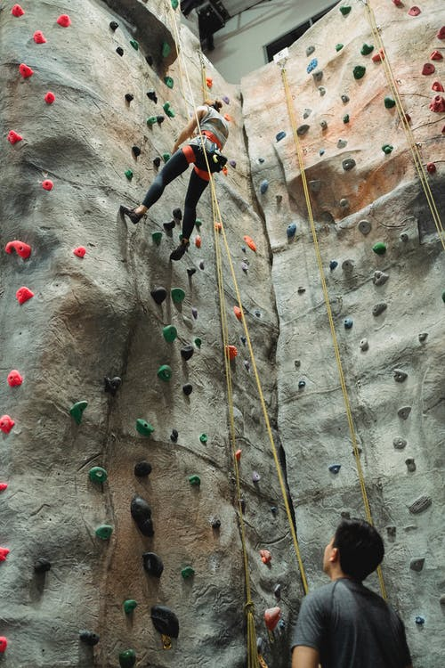 From below of unrecognizable male instructor looking at female climber practicing bouldering on colorful artificial rock in climbing gym