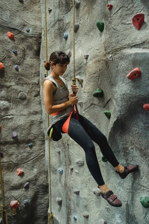Side view of young fit Asian female climber in sportswear hanging on belay rope during bouldering workout in gym