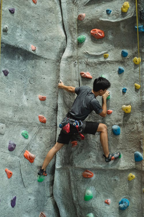 Unrecognizable male boulderer climbing wall in gym