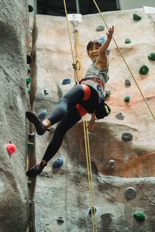 From below side view of positive young ethnic lady in sportswear and harness smiling while hanging on belay rope during bouldering workout in gym
