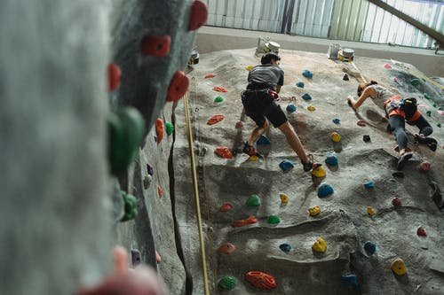 Anonymous boulderers climbing steep wall during indoor training