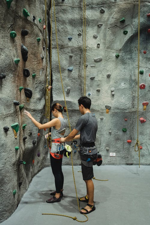 Anonymous male and female climbers preparing for ascending wall in gym