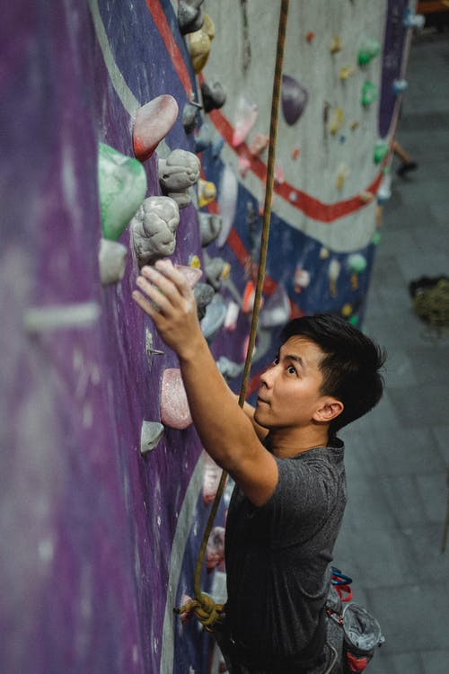 Focused strong young Asian guy climbing wall in gym