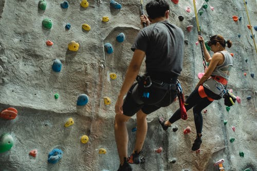 Anonymous mountaineers hanging on belay during climbing wall in gym