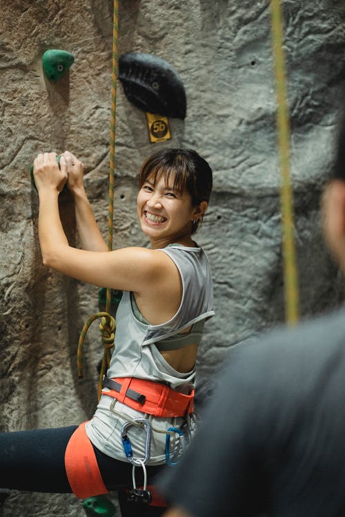 Side view of cheerful young Asian female beginner climber in activewear and safety harness smiling and looking at crop anonymous trainer while grabbing grip during bouldering workout