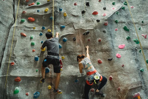 Unrecognizable athletes practicing climbing in bouldering gym