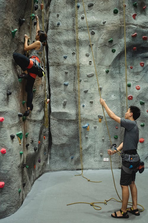 Side view of anonymous young ethnic male trainer in activewear holding belay rope while female climber ascending wall in gym