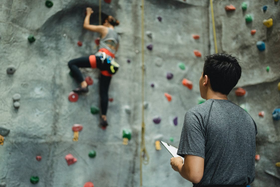 Anonymous male trainer controlling female climber ascending wall