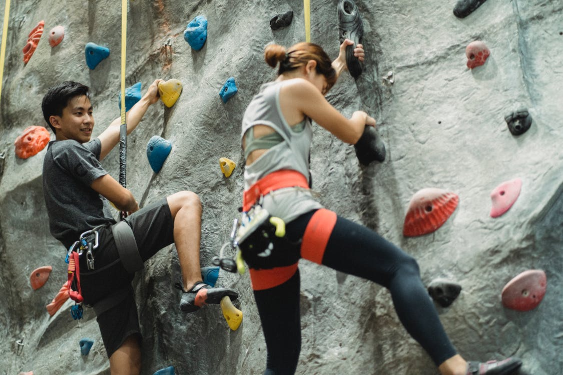 Low angle of young Asian male and female friends in sportswear and protective harness practicing bouldering together in climbing gym