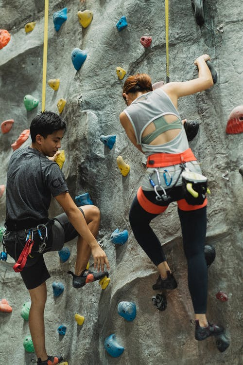From below back view of young Asian male mountaineer with unrecognizable sportswoman climbing wall with grips while practicing extreme sport