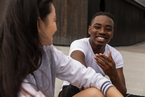 Cheerful young African American guy in casual clothes smiling while chilling on street with crop Asian female friend