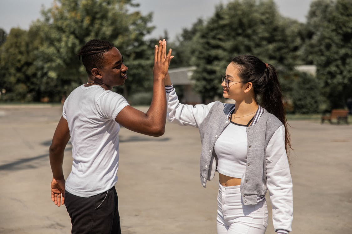Side view of content young African American man and Asian woman in casual outfits giving high five and smiling while chilling together in park
