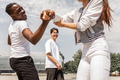 Joyful multiethnic friends having fun together on city square