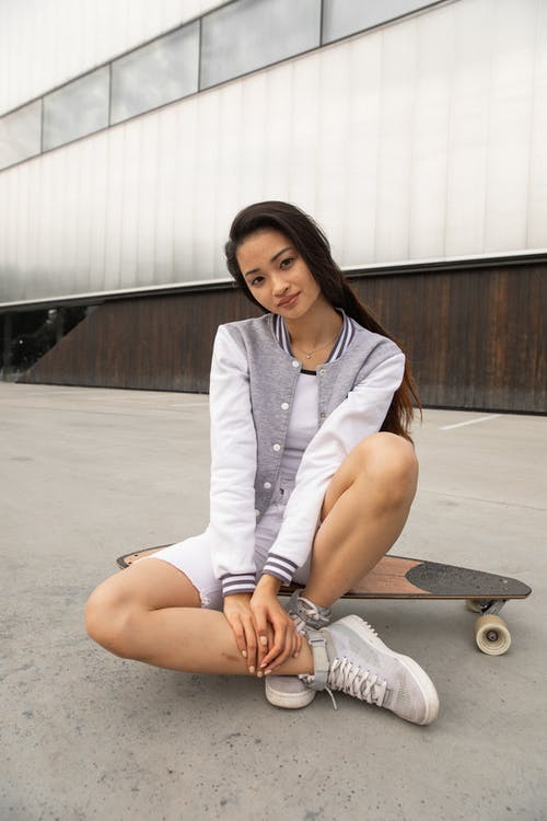 Full body of confident young fit Asian female millennial with long dark hair in stylish outfit sitting on longboard while resting on street after skating