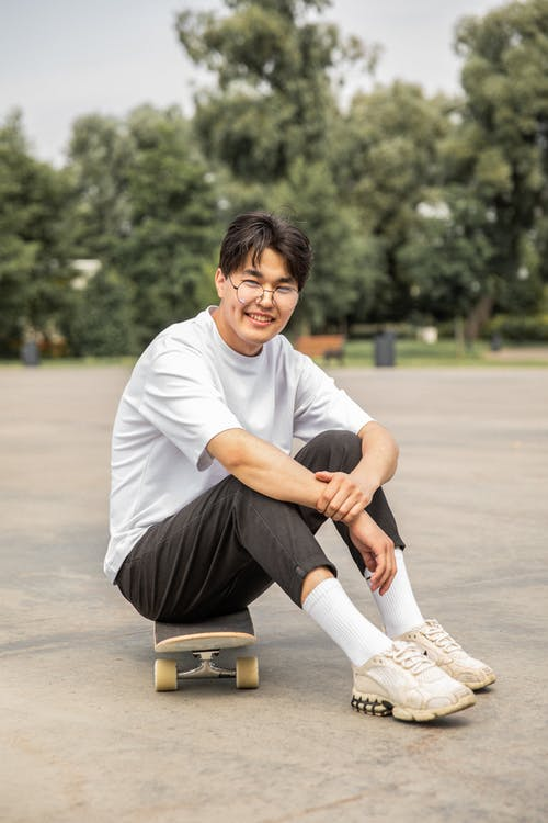 Full length of positive young Asian male skater in stylish outfit and eyeglasses sitting on board and smiling while resting after training in park
