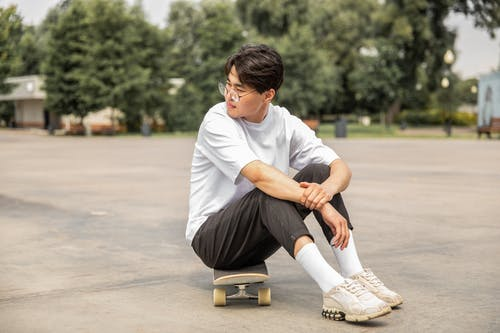 Full body of pensive ethnic male teenager in trendy outfit and eyeglasses sitting o skateboard and looking away while resting in park after training